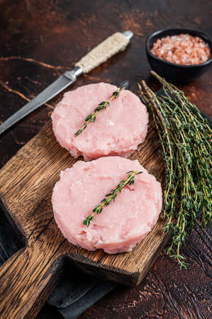 Fresh Raw burgers patty cutlet from chicken and turkey meat with herbs. Dark background. Top view