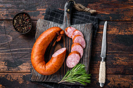 German Smoked sausage on a wooden rustic board with thyme. Dark wooden background. Top view 免版税图像