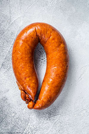 Smoked sausage on a white rustic table. White background. Top view 免版税图像