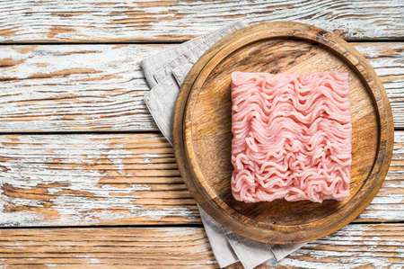 Raw mince or ground chicken meat on wooden board. White background. Top view. Copy space