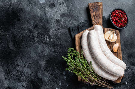 Raw Munich white sausage weisswurst on wooden board. Black background. Top view. Copy space