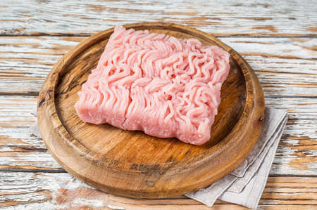 Raw mince or ground chicken meat on wooden board. White background. Top view