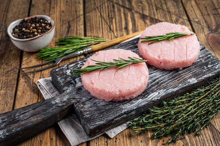 Raw burgers patty from organic chicken and turkey meat with thyme and rosemary. wooden background. Top view