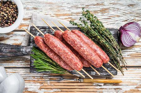 Raw kofta or lula kebabs meat sausages on skewers with herbs. Dark wooden background. Top view