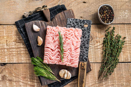Raw minced chicken and turkey meat on wooden chopping board with butcher cleaver. wooden background. Top view 免版税图像 - 168547979