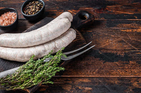 Munich traditional white sausages on a wooden board with thyme. Dark wooden background. Top view. Copy space