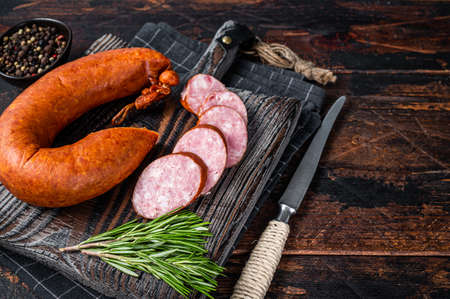 German Smoked sausage on a wooden rustic board with thyme. Dark wooden background. Top view. Copy space