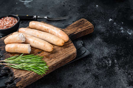 Roasted chicken and turkey sausages on a wooden board. Black background. Top view. Copy space