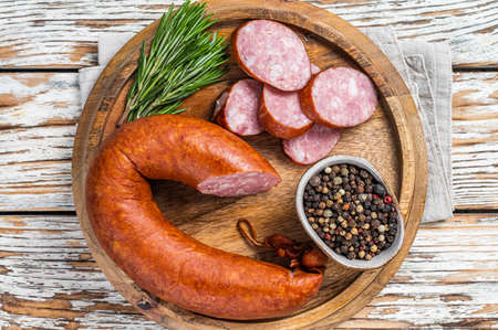 Bavarian Smoked sausage on a wooden board with herbs. White wooden background. Top view 免版税图像