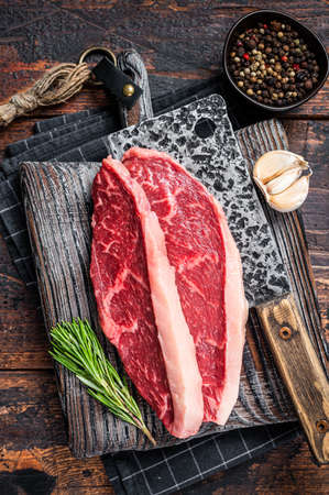 Raw top sirloin cap beef meat steaks on butcher board with meat cleaver. Dark woden background. Top view