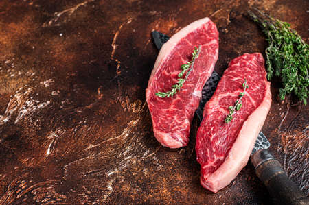 Uncooked Raw top sirloin cap or rump beef meat steaks on a butcher knife. Dark background. Top view. Copy space