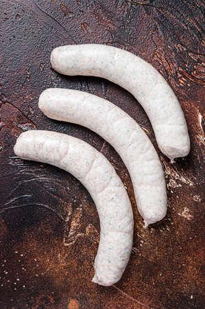 Raw German white sausage weisswurst on kitchen table. Dark background. Top view