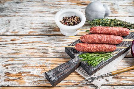 Raw kofta or lula kebabs meat sausages on skewers with herbs. Dark wooden background. Top view. Copy space