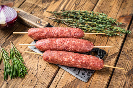 Fresh Raw kofta or lula kebabs skewers on a butcher cleaver with herbs. wooden background. Top view