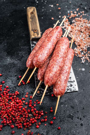 Raw lula or kofta kebabs skewers on a butcher cleaver with salt and pepper. Black background. Top view 免版税图像