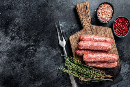 Uncooked Raw beef and lamb meat kebabs sausages on a wooden board. Black background. Top view. Copy space