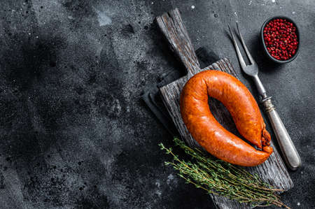 Bavarian Smoked sausage on a wooden rustic board with thyme. Black background. Top view. Copy space 免版税图像 - 168548022