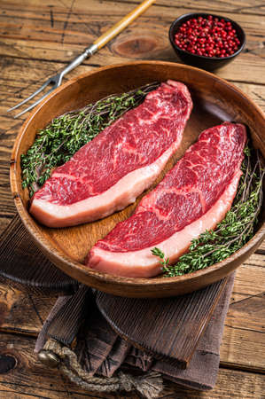 Uncooked Raw top sirloin cap beef meat steaks in a wooden plate with herbs. woden background. Top view