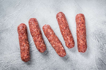 Raw beef and lamb meat kebabs sausages on a butcher table. White background. Top view 免版税图像 - 168548026