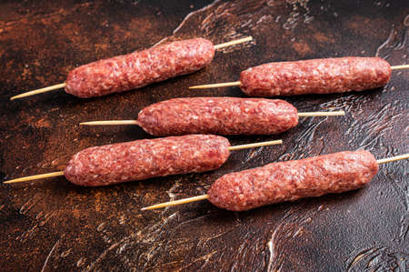 Raw kofta meat kebabs sausages on skewers. Dark background. Top view