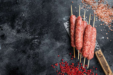 Raw lula or kofta kebabs skewers on a butcher cleaver with salt and pepper. Black background. Top view. Copy space