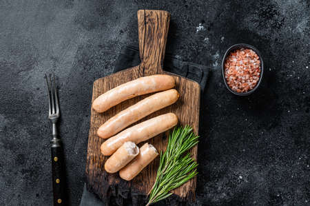 Roasted chicken and turkey sausages on a wooden board. Black background. Top view 免版税图像 - 168548032