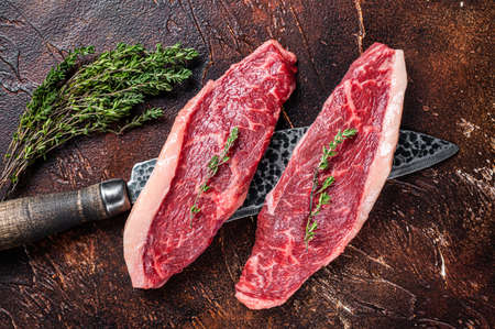 Uncooked Raw top sirloin cap or rump beef meat steaks on a butcher knife. Dark background. Top view