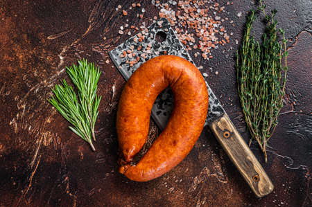 Hot Smoked sausage on a butcher rustic cleaver with herbs. Dark background. Top view