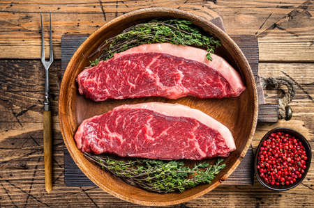 Uncooked Raw top sirloin cap beef meat steaks in a wooden plate with herbs. woden background. Top view 免版税图像 - 168548038
