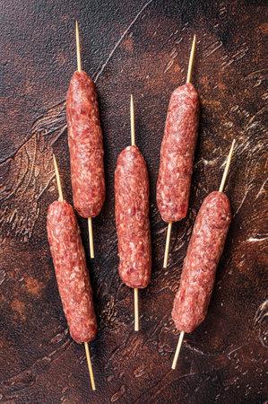 Raw kofta meat kebabs sausages on skewers. Dark background. Top view 免版税图像 - 168548039