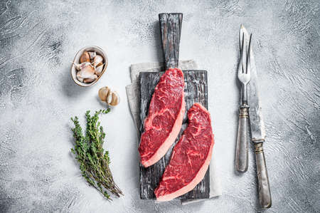 Raw rump beef meat steaks on wooden board with meat knife and fork. White background. Top view 免版税图像 - 168548040