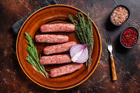 Raw kofta meat kebabs sausages on a plate with herbs. Dark background. Top view 免版税图像