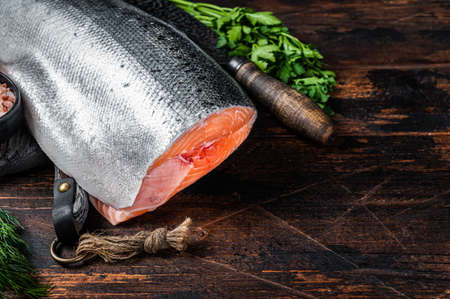Big piece of Raw cut salmon fish on a wooden cutting board with chef knife. Dark Wooden background. Top view. Copy space