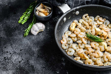 Roasted cooked Peeled Shrimps, Prawns in a pan. Black background. top view. copy space