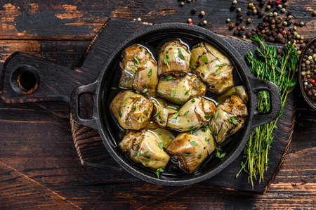 Marinated artichokes in olive oil in a pan. Dark wooden background. Top view