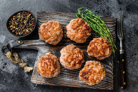 Roasted cutlets from beef and pork meat. Black background. Top view 免版税图像