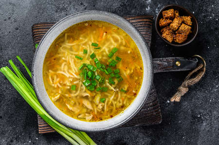 Fresh homemade chicken soup with noodle at table. Black background. Top view