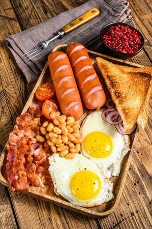 English Breakfast in a wooden tray with fried eggs, sausages, bacon, beans and toasts. wooden background. top view