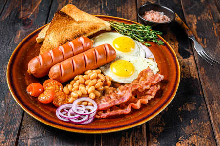 Traditional Full English breakfastt with fried eggs, sausages, bacon, beans and toasts. Dark wooden background. top view