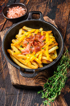 French fries with melted mix of cheddar cheese and bacon served in a pan. Dark wooden background. Top view