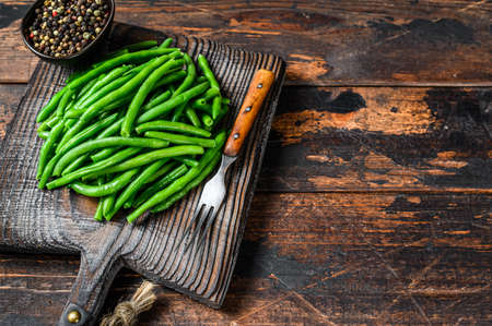 Fresh green beans on a cutting board. Dark wooden background. top view. Copy space