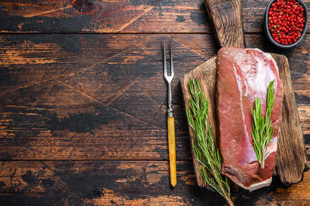 Raw fresh duck meat breast fillet steak with herbs and rosemary. Dark wooden background. Top view. Copy space