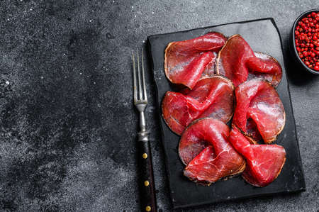 Bresaola cured meat beef cut pieces, Italian Antipasti. Black background. Top view. Copy space 免版税图像