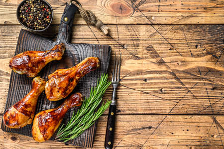 Barbecue roasted chicken drumsticks on a wooden cutting board. wooden background. top view. Copy space