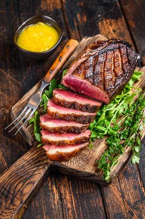 Sliced grilled duck meat fillet steak. Dark wooden background. Top view
