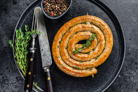 Roasted spicy spiral meat sausage on a plate. Black background. Top view 免版税图像