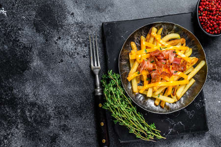 Delicious golden French fries with melted cheddar cheese and bacon. Black background. Top view. Copy space 免版税图像
