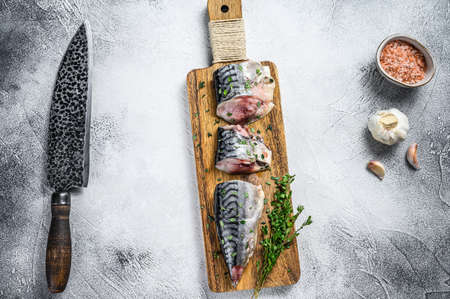 Sliced salted mackerel fish on a wooden cutting board. White background. Top view 免版税图像