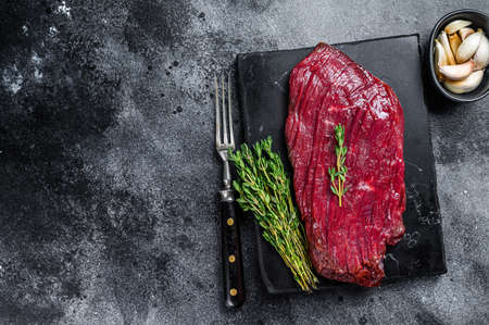 Venison raw steak from wild meat. Black background. Top view. Copy space 免版税图像