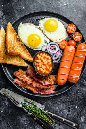 English breakfast with fried eggs, sausages, bacon, beans and toasts in a plate. Black background. top view